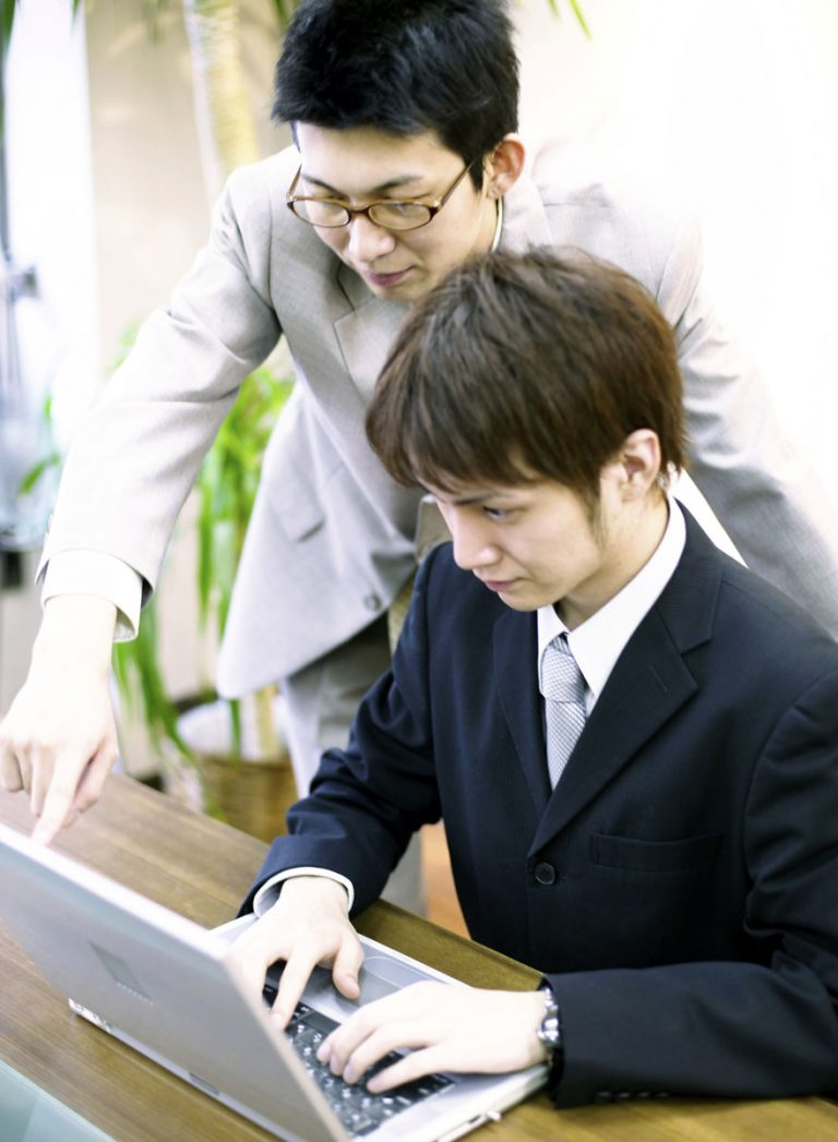 Businessmen Working on Laptop Together --- Image by © Bloomimage/Corbis